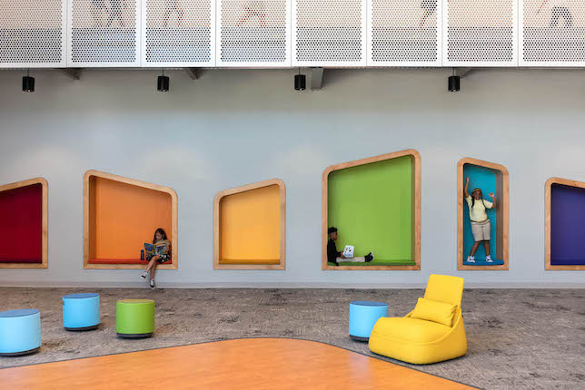 Bright, colorful niches in the media center allow students to play within the walls.