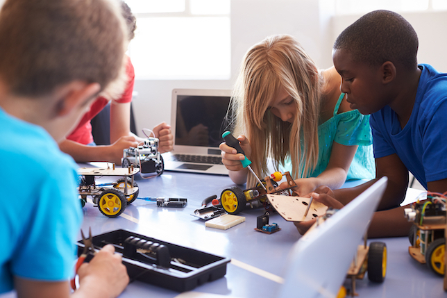 Children using tools like a screwdriver to tinker with a robot on a table.