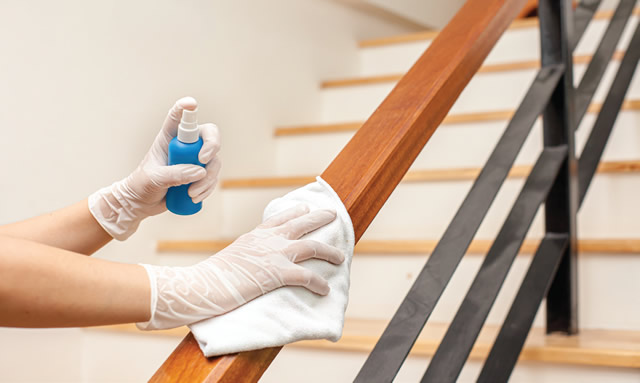 cleaning hand rails on staircase