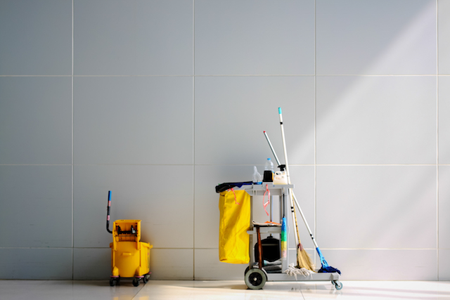 A custodian cart in front of a white wall.