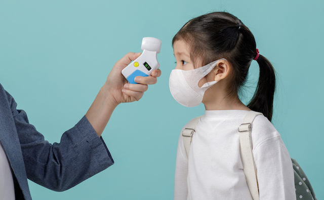 Woman taking the temperature of a child who is wearing a face mask and a backpack with a contactless thermometer.