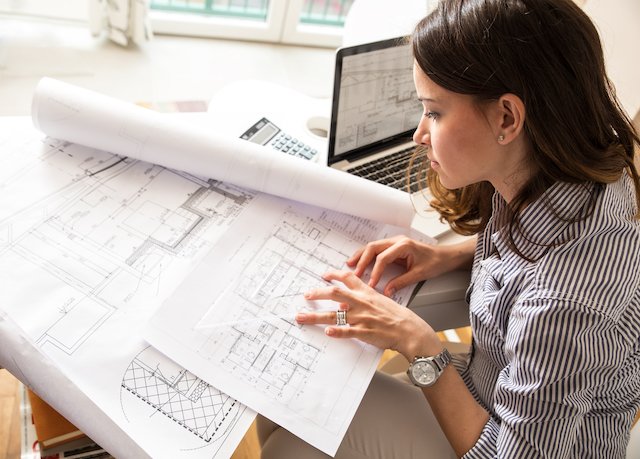 A woman architect looking at blueprints with her laptop open.