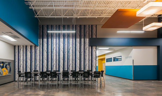 The volume of the existing structure of CEC Fort Collins High School offered an opportunity to bring daylight in from above, creating a community space within the hallway.