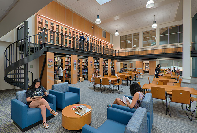 The design team added a new mezzanine level with a spiral staircase which doubles as a gallery space to display the school's 125-year-old journalism archives and rare books collections.