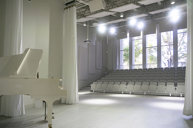 Audience Systems outfitted the white box theater with custom all-white seating.