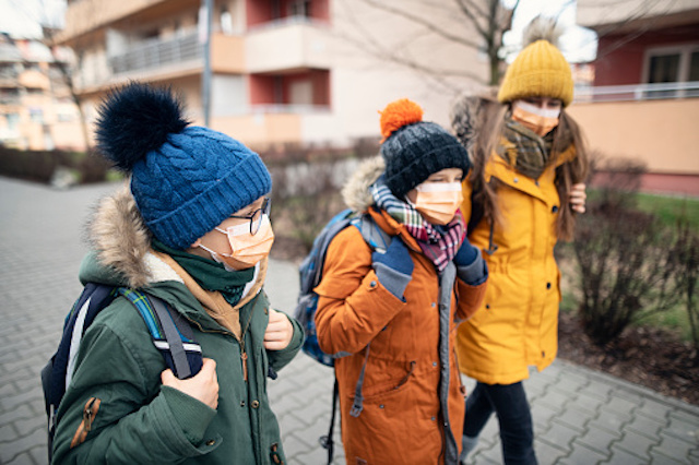Children in winter coats and hats wearing face masks and walking on sidewalk.