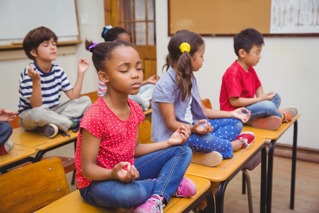 Children meditating in a classroom.
